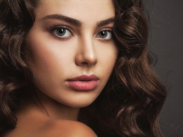 Close-upgezicht van een mooie vrouw met een rokerige oogmake-up. sexy en prachtige bruinharige vrouw met lang krullend haar. portret van het aantrekkelijke vrouwelijke stellen.