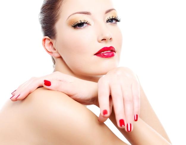 Close-upgezicht van een sensualiteitvrouw met rode heldere manicure en lippen