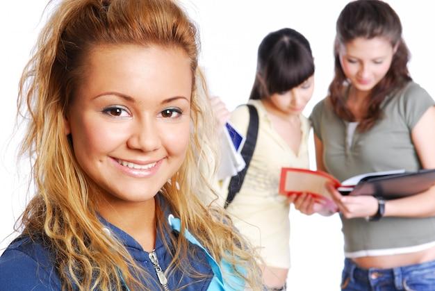 Close-upgezicht van leuke vrouwelijke student - nadruk op voorgrond. ðžn achtergrond staande klasgenoten.