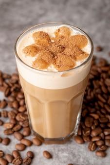 Close-upglas cappucino met koffiebonen