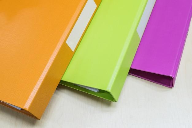 Close-upgroep kleurrijk documentdossier op houten bureauachtergrond