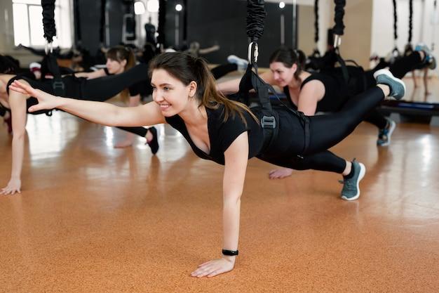 Close-upgroep meisjes die op bungeelastiekjes hangen in de gymnastiek. meisjes doen een moeilijke oefening met bungee-kauwgom