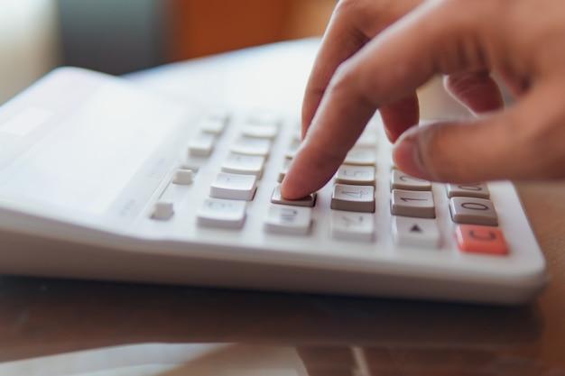 Close-uphand die calculator gebruiken die als zaken en financieel concept gebruiken