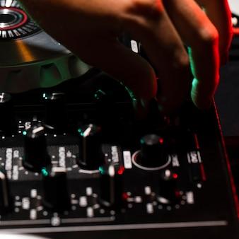 Close-uphand die de console van dj aanpassen