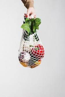 Close-uphand die ecologische kruidenierswinkelszak houden