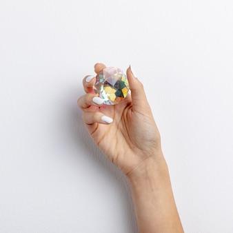 Close-uphand die een kleurrijk kristal houden