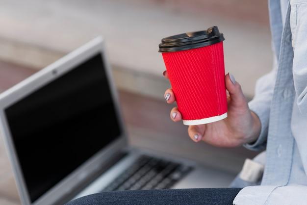 Close-uphand die een kop van koffie houden