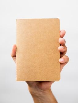 Close-uphand die een notitieboekjemodel tonen