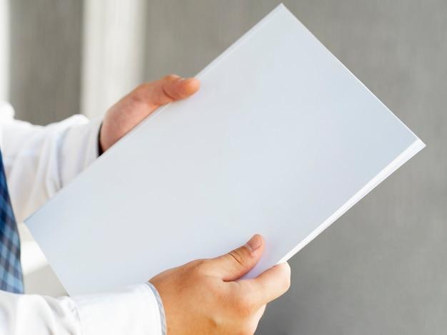 Close-uphand die een stapel van document model tonen