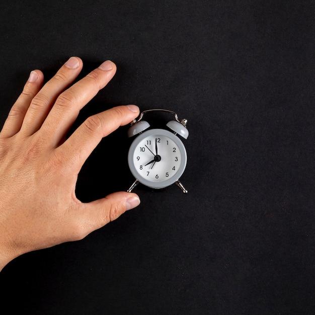 Close-uphand die een uitstekende klok schikken