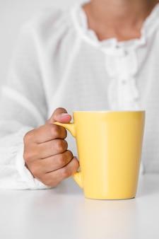 Close-uphand die gele mok houden