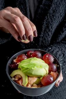 Close-uphand die gezonde salade met zout bestrooien