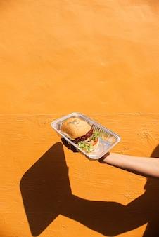 Close-uphand die heerlijke hamburger steunen