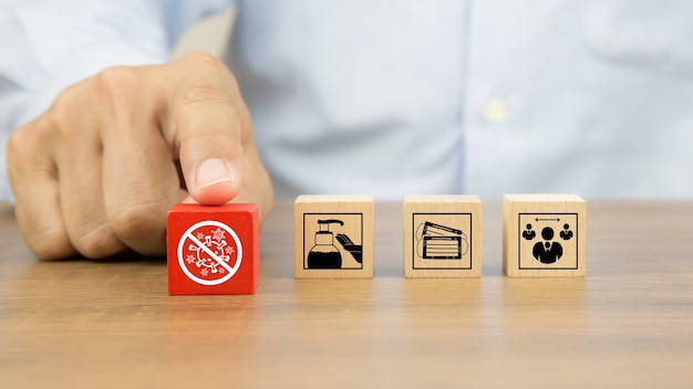 Close-uphand die het pictogram van de covidbescherming op houten stuk speelgoed kiezen