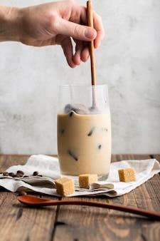 Close-uphand die ijs latte met melk voorbereiden