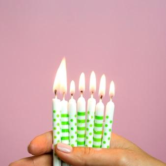 Close-uphand die kleine verjaardagskaarsen houden