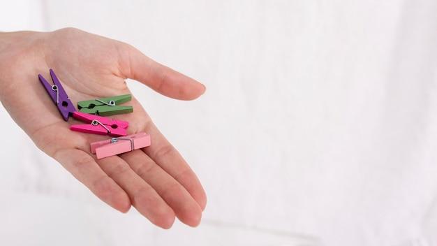 Close-uphand die kleurrijke wasknijpers houden