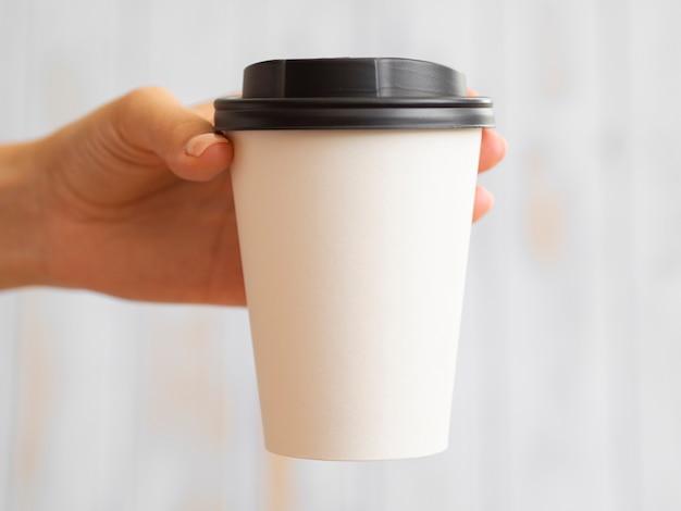 Close-uphand die koffiekop steunen