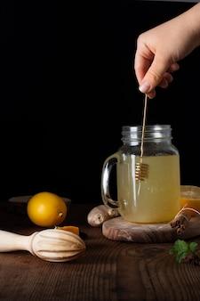 Close-uphand die kruik mengen die met eigengemaakte limonade wordt gevuld