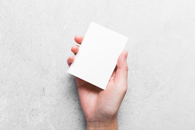 Close-uphand die leeg adreskaartje houden
