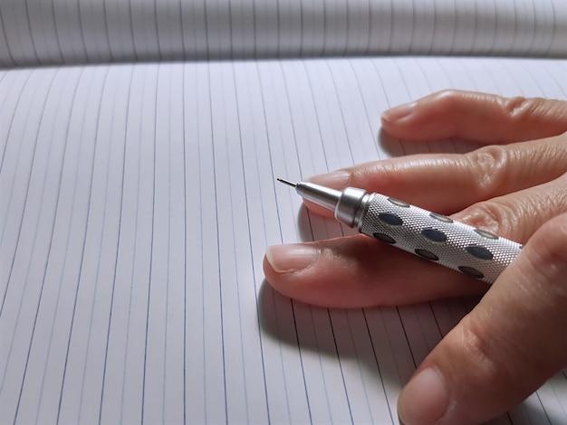 Close-uphand die mechanisch potlood op notitieboekjedocument houdt