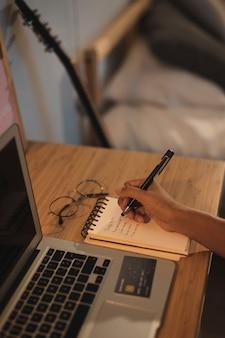 Close-uphand die op een notitieboekje schrijven