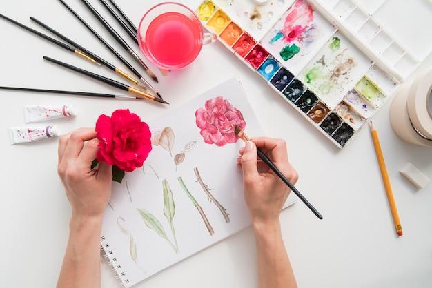 Close-uphand die rode bloem houden