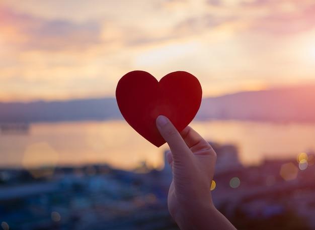 Close-uphand die rood hart houden tijdens zonsondergangachtergrond