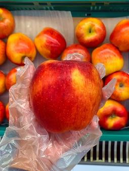 Close-uphand die transparante handschoen draagt die rode appel uit mand bij supermarkt plukt, wegwerphandhandschoen beschermt infectie tijdens voedselinkopen