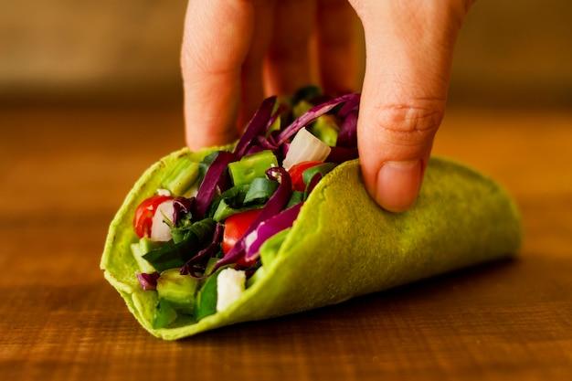 Close-uphand die vegetarische taco houden