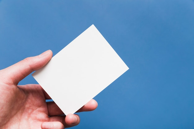 Close-uphand die wit adreskaartje houden