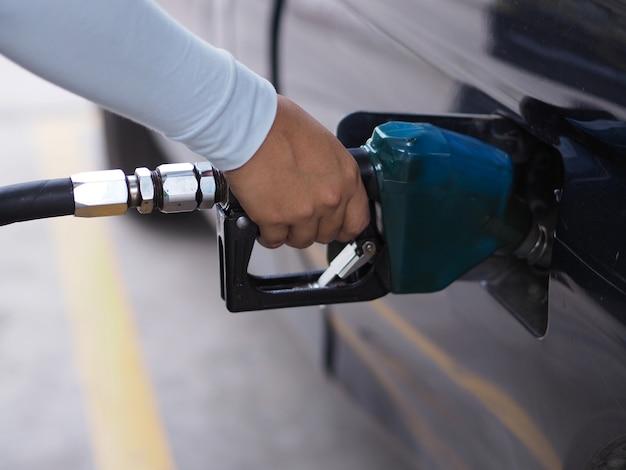 Close-uphand man pompende benzinebrandstof in auto bij benzinestation.