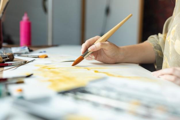 Close-uphand met borstel het schilderen