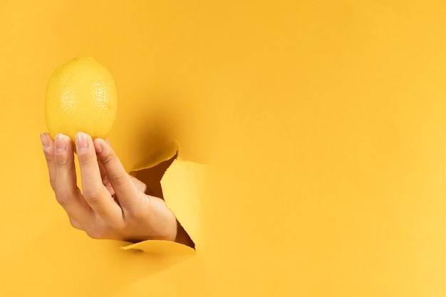 Close-uphand met citroen en exemplaarruimte