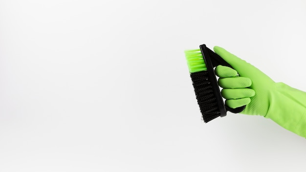 Close-uphand met groene handschoen en zwarte borstel