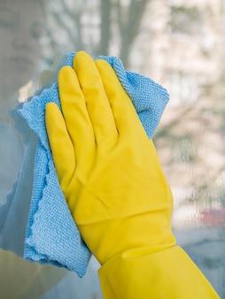 Close-uphand met het rubberen handschoen schoonmakende venster