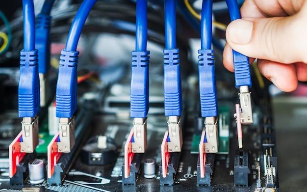 Close-uphand sluit een kabel aan op sleuf voor het bouwen van een apparaat voor cryptocurrency-mining als altcoins of bitcoin. connectoren op het moederbord voor grafische kaarten.