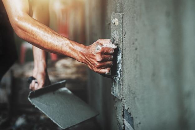 Close-uphand van arbeider het pleisteren cement bij muur voor de bouw van huis