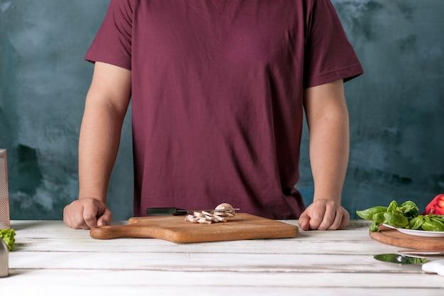 Close-uphand van chef-kokbakker die pizza maken bij keuken
