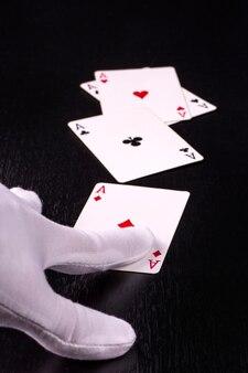 Close-uphand van de dealer in witte handschoenen in een casino die kaarten uitdeelt op een donkere tafel
