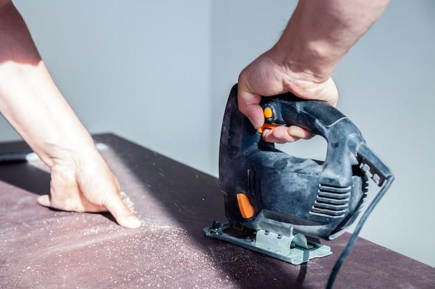 Close-uphand van schrijnwerker met professionele snijgereedschap figuurzaag of decoupeerzaag, gesneden houten tafelblad, zaagplank, bruin vijlsel, zaagsel. snij een gat voor de wastafel in de badkamer