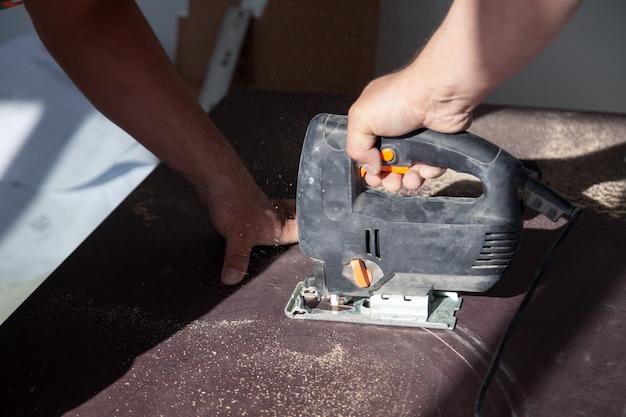 Close-uphand van schrijnwerker met professionele snijgereedschapzaag
