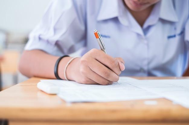 Close-uphand van studenten die een examen in klaslokaal met spanning schrijven