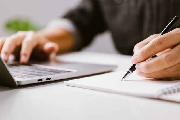 Close-uphand van zakenman die op nota schrijft terwijl het gebruiken van laptopcomputer op bureau thuis