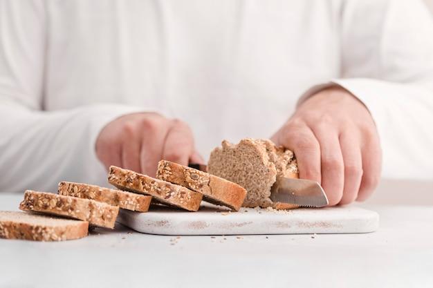 Close-uphanden die brood snijden