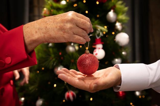 Close-uphanden die kerstmisbal houden
