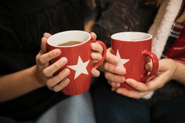Close-uphanden die koffiemokken houden