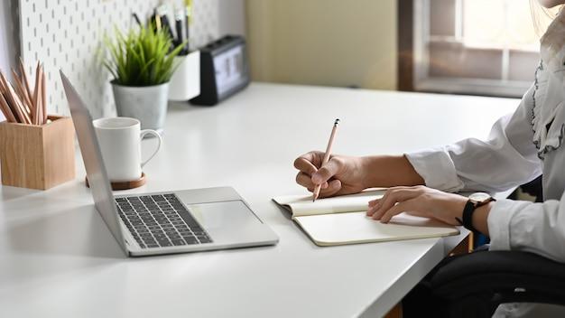 Close-uphanden die op notitieboekjedocument schrijven