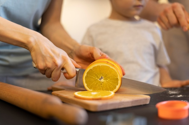 Close-uphanden die sinaasappel snijden