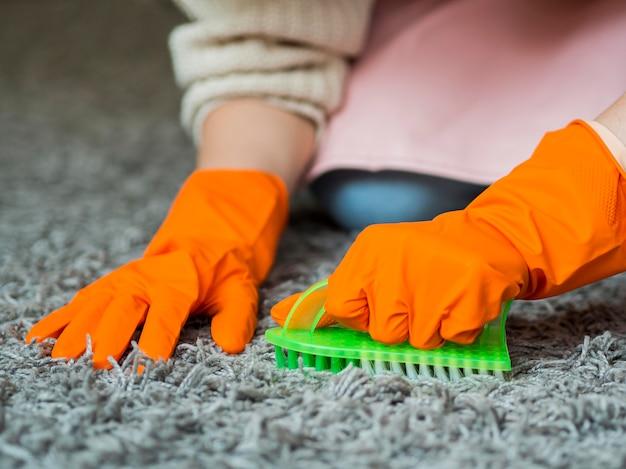 Close-uphanden die tapijt borstelen